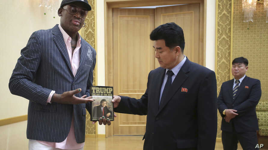 "Former NBA basketball star Dennis Rodman presents a book titled ""Trump The Art of the Deal"" to North Korea's Sports Minister Kim Il Guk Thursday, June 15, 2017, in Pyongyang, North Korea. (AP Photo/Kim Kwang Hyon)"