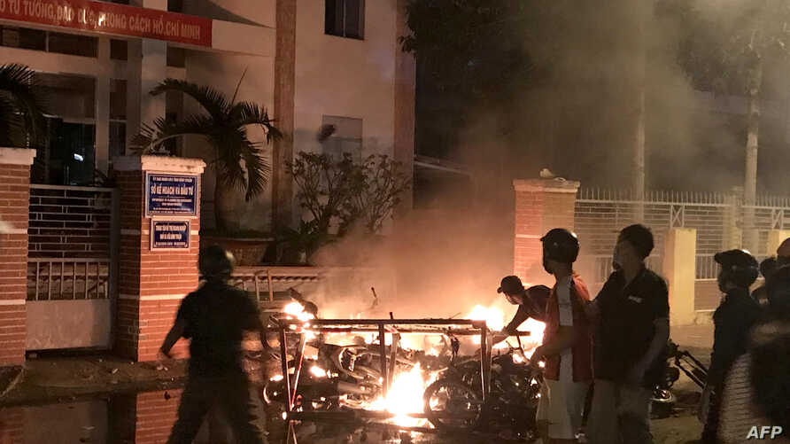 FILE - This June 10, 2018, picture shows protesters burning motorcycles in front of a provincial office in Vietnam's south central coast Binh Thuan province in response to legislation on three special economic zones that would grant 99-year leases to