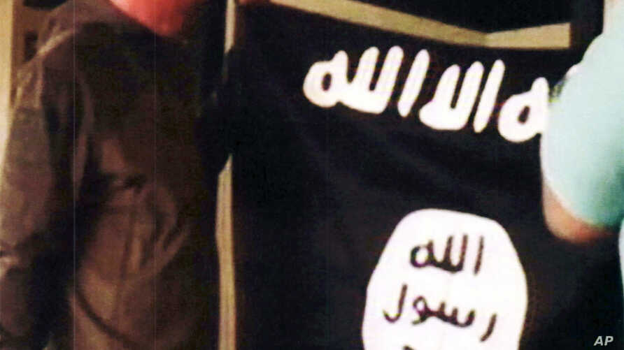 FILE - In this July 8, 2017 file image taken from FBI video and provided by the U.S. Attorney's Office in Hawaii on July 13, 2017, Army Sgt. 1st Class Ikaika Kang holds an Islamic State group flag after allegedly pledging allegiance to the terror gro