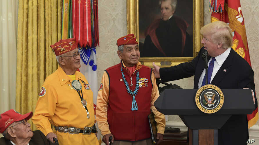 President Donald Trump, right, speaks about Sen. Elizabeth Warren, D-Mass., during a meeting with Navajo Code Talkers including, from left, Fleming Begaye Sr., Thomas Begay, and Peter MacDonald, in the Oval Office of the White House in Washington, Mo