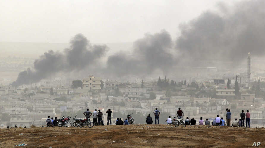 People on a hilltop watch smoke rising from a fire caused by a strike in Kobani, Syria, during fighting between Syrian Kurds and the militants of Islamic State group, on the outskirts of Suruc, at the Turkey-Syria border, Oct. 11, 2014.