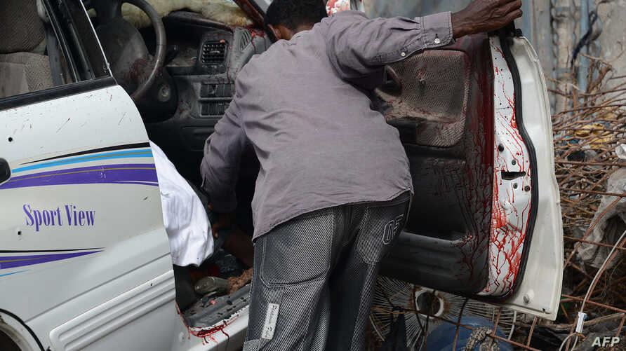 A resident tries to remove the remains of the driver of the female MP and former singer Sado Ali Warsame after gunmen opened fire at her car on July 23, 2014 killing her and her driver in  Mogadishu.