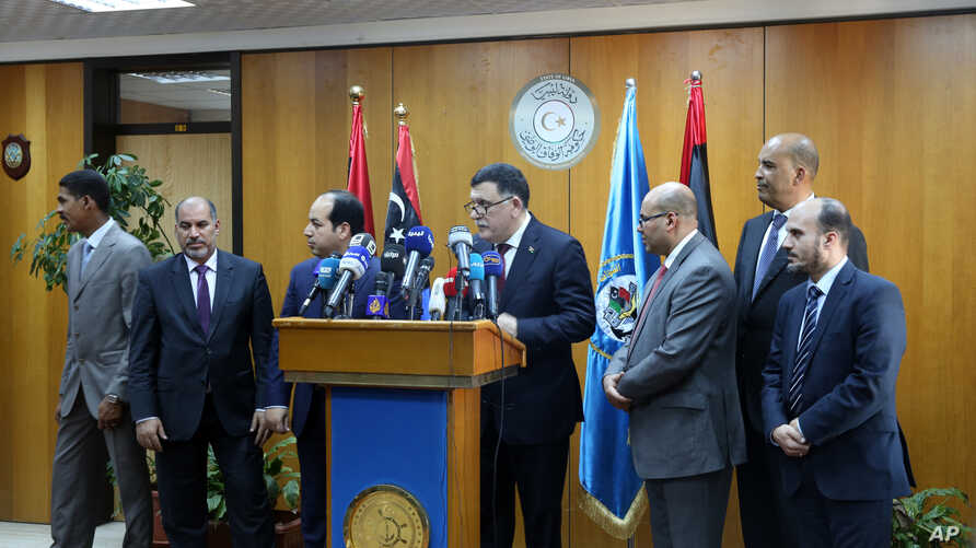 Fayez Seraj, flanked by members of the Presidential Council, speaks during a news conference at the Mitiga Naval Base in Tripoli, Libya, March, 30, 2015.