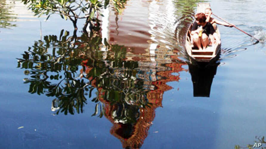 A man rows his passenger on a boat past the shadow of the flooded Chatkaew Chongkolnee temple in Bangkok, Thailand, November 1, 2011.