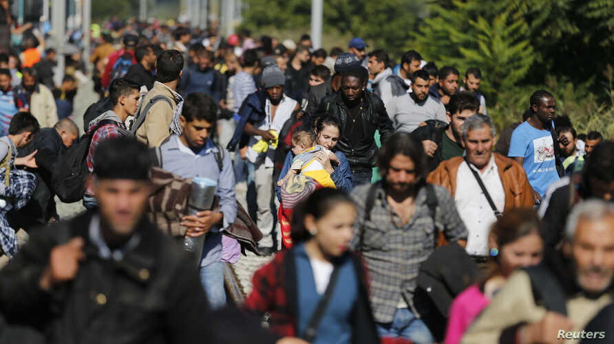 Migrants disembark from a train after arriving at the station in Botovo, Croatia, Sept. 23, 2015, before walking to the Hungarian border.