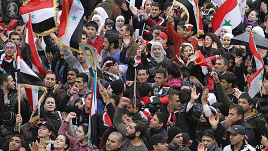 Syrians wave national flags as they rally in central Damascus in support of President Bashar al-Assad's, Nov. 16, 2011.