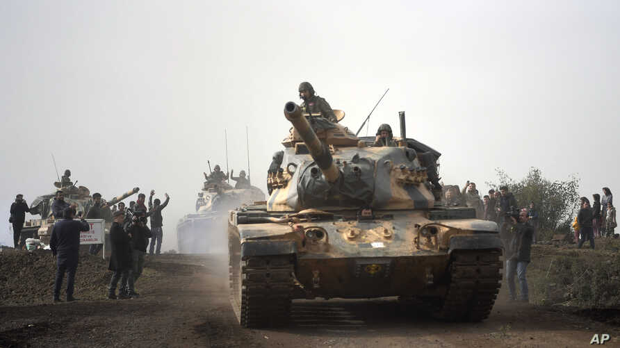Turkish army tanks enter Afrin, an enclave in northern Syria controlled by U.S.-allied Kurdish fighters, in Hassa, Hatay, Turkey, Jan. 22, 2018.