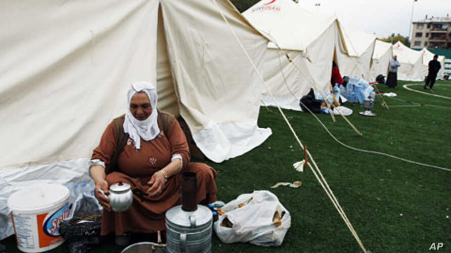 An earthquake survivor washes dishes outside her tent in a tent city set up in a soccer field in Ercis, Van, Turkey, October 27, 2011.