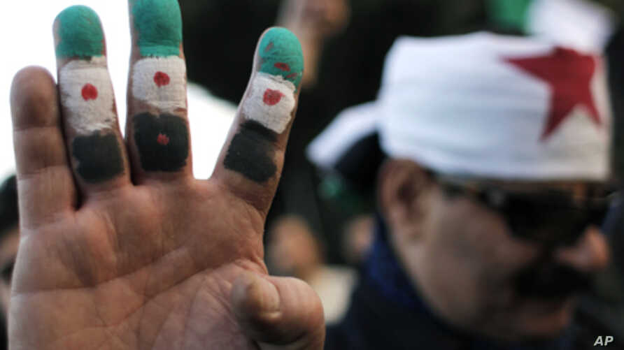 An anti-Syrian regime protester colors his fingers with the revolutionary flag colors during a protest outside the Arab League headquarters in Cairo, Egypt Sunday, Jan. 22, 2012.