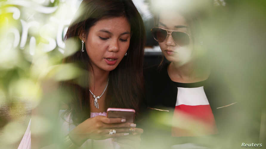 FILE - Online activist Thy Sovantha, 19, left, and a friend use their mobile phones and social media in a cafe in Phnom Penh, Dec. 11, 2014.