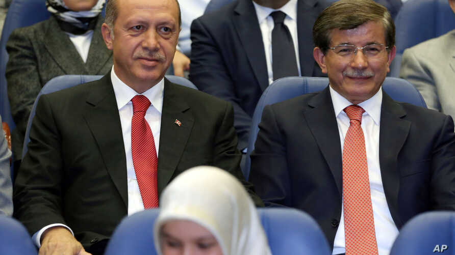 Turkey's president-elect Recep Tayyip Erdogan (L) and Foreign Minister Ahmet Davutoglu sit together during a party meeting in Ankara, Turkey, Aug. 21, 2014.