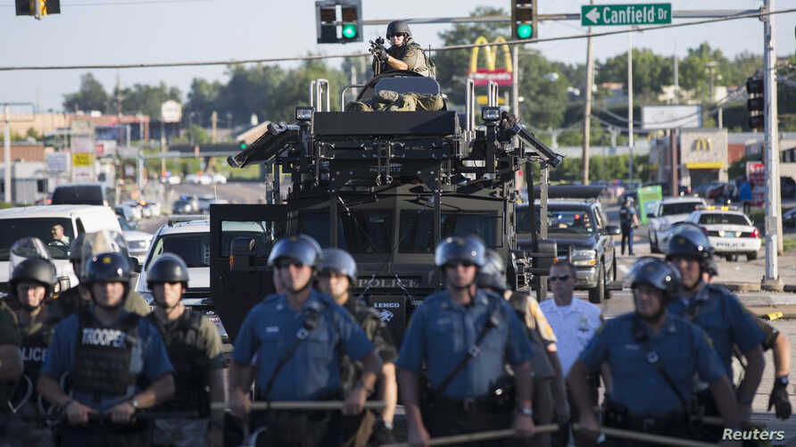 Riot police stand guard as demonstrators protest the shooting death of teenager Michael Brown in Ferguson, Missouri August 13, 2014. Police in Ferguson fired several rounds of tear gas to disperse protesters late on Wednesday, on the fourth night of ...