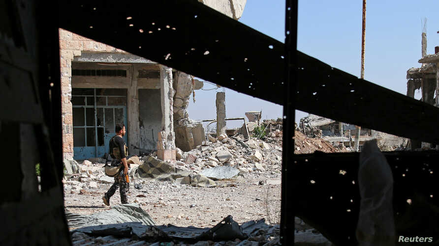 A Free Syrian Army fighter carries his weapon as he walks past damaged buildings in a rebel-held part of the southern city of Deraa, Syria, July 9, 2017.
