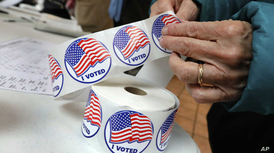 """A voter retrieves her """"I Voted"""" sticker after casting her ballot at the Presbyterian Church of Mount Kisco, in Mt. Kisco, N.Y. Tuesday, Nov. 6, 2018."""