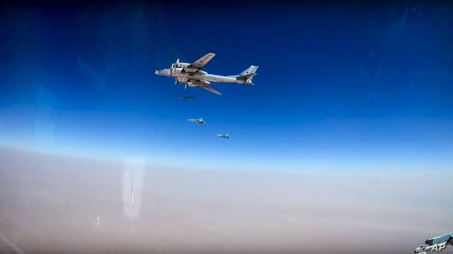 In this photo made from the footage taken from Russian Defense Ministry official web site on Wednesday, July 5, 2017 Russian strategic T-95 bomber, with Russian jet fighters at rear, launches X-101 cruise missiles on IS facilities in the area along t