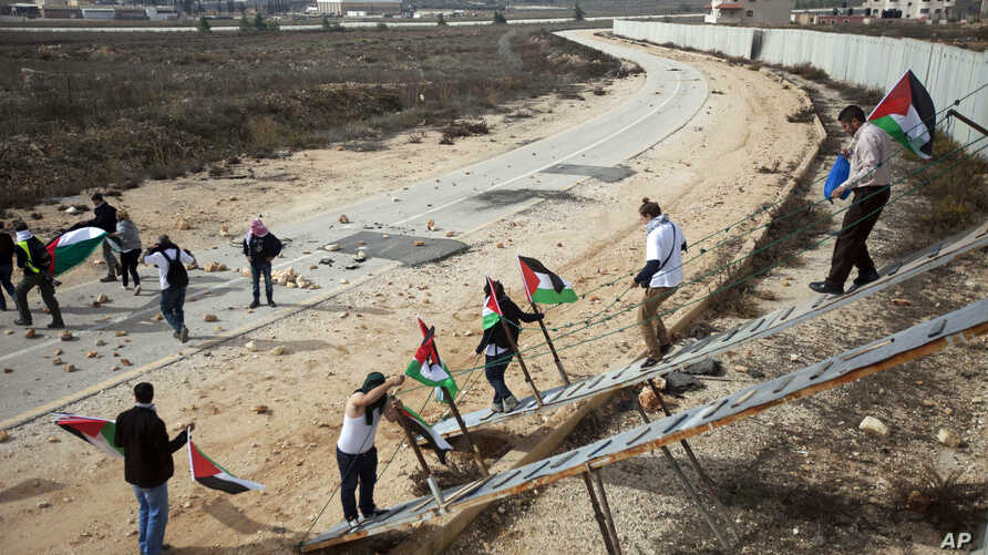 Palestinian activists use ladders to cross over the Israeli separation barrier to pray on Friday at the al-Aqsa Mosque in the Old City of Jerusalem, Nov. 14, 2014.