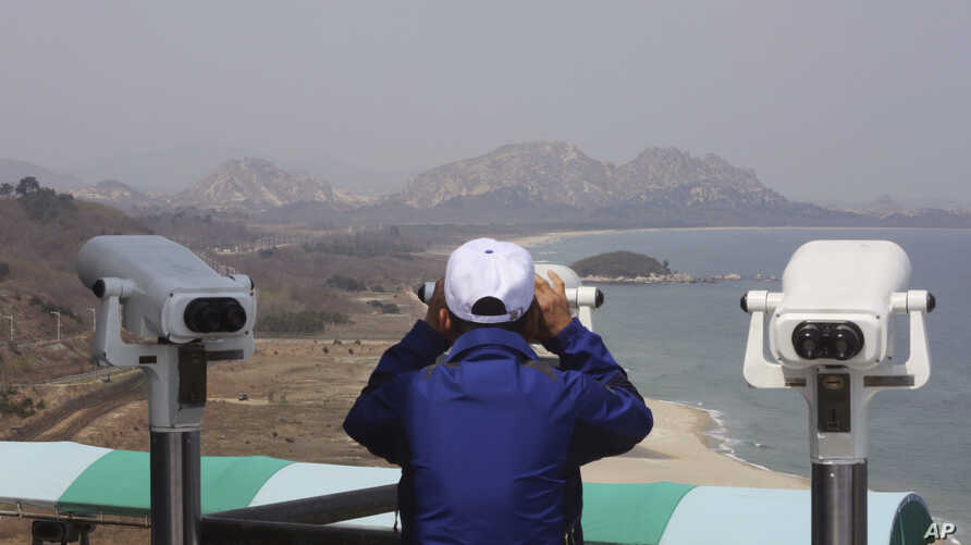 A South Korean tourist uses binocular to look at the Diamond Mountain in North Korea from the Unification Observation post in Goseong, South Korea,  April 7, 2017.