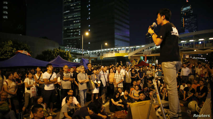 Pro-democracy protesters listen to a student's speech outside the government headquarters office in Hong Kong October 10, 2014. Hundreds of protesters regrouped in central Hong Kong on Friday to push their call for democracy, a day after the governme