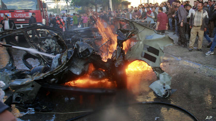 People look at a wreckage of the car in which Ahmed al-Jaabari  was killed, Gaza City, November 14, 2012.