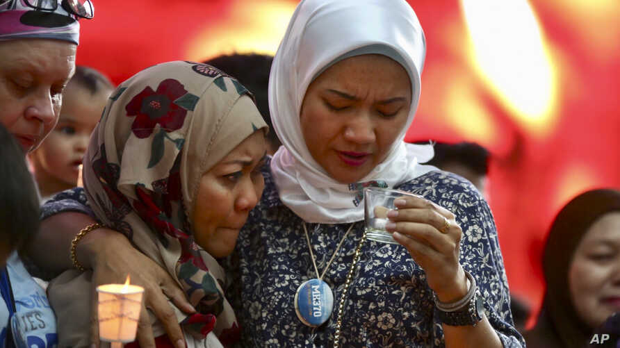 Norazlinda Ayub, left, and Intan Maizura Othaman, wife of an air crew member of Malaysia Airlines Flight 370, embrace each other during the Day of Remembrance for MH370 event in Kuala Lumpur, Malaysia, March 3, 2019.