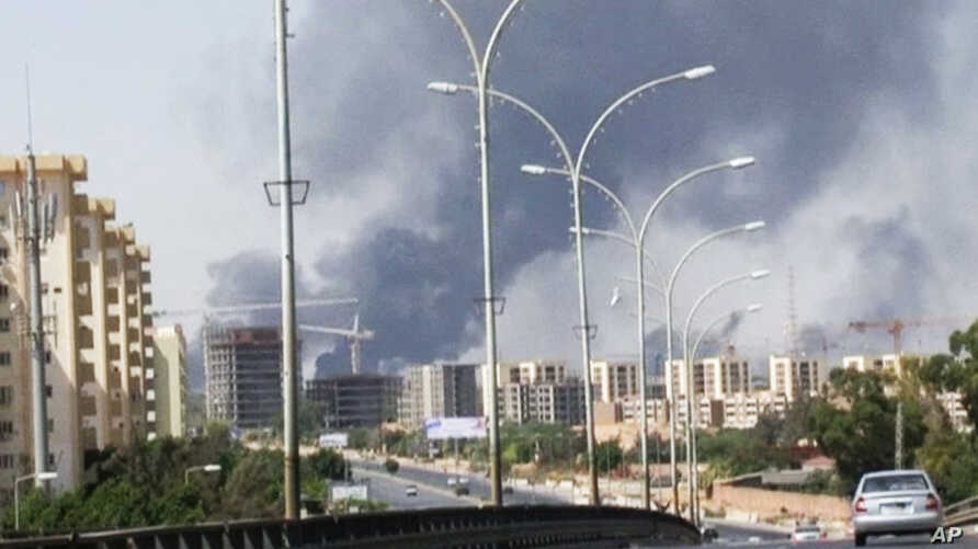 In this image made from video by The Associated Press, smoke rises from the direction of Tripoli airport in Tripoli, Libya, July 13, 2014.