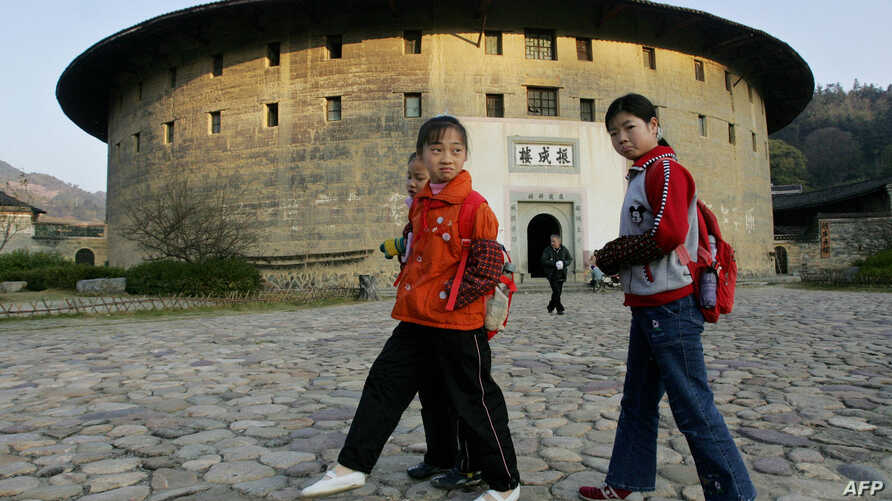 FILE - Schoolchildren pass by an old circular Tulou earth house, which are the traditional homes of China's minority Hakka people, in Yongding village, Fujian Province,  December 15, 2005.
