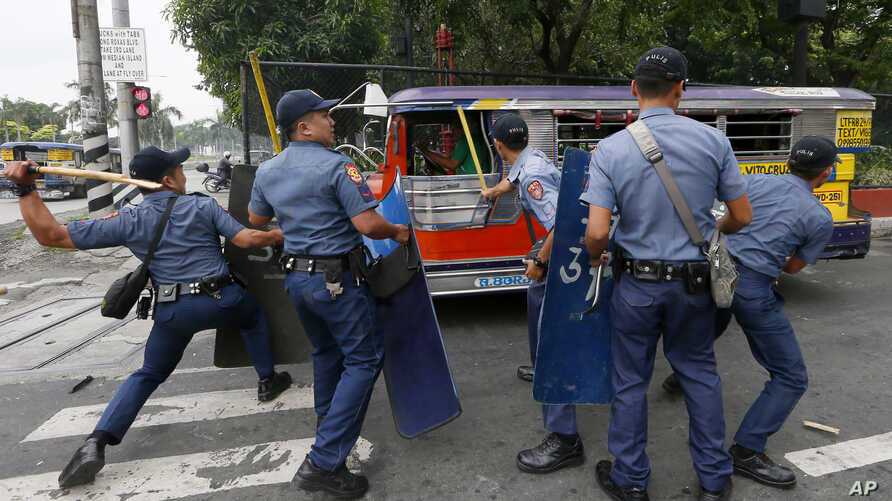 Police officers hit fleeing protesters during a violent dispersal outside the U.S. Embassy in Manila, Philippines, Oct. 19, 2016.