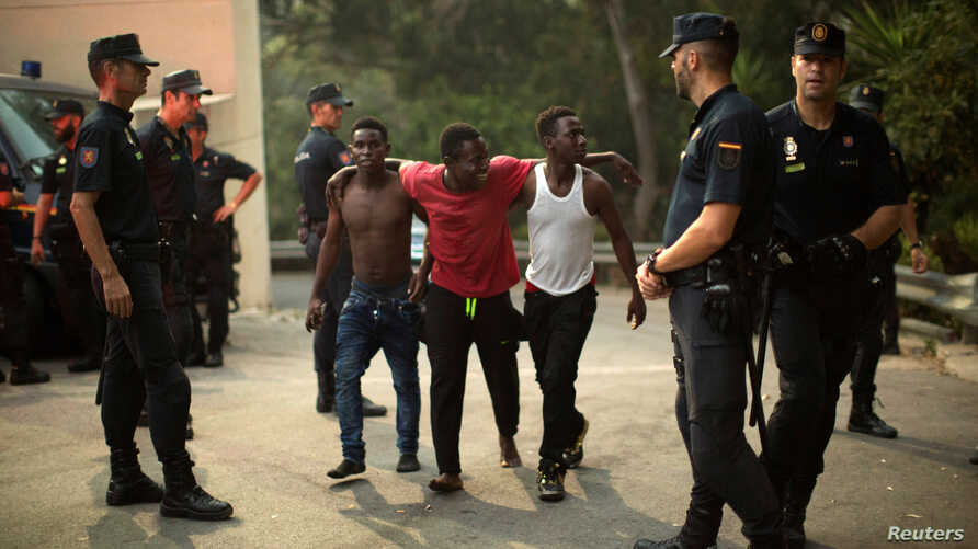 Police stand around a group of African migrants after they crossed the border fence from Morocco to Spain's North African enclave of Ceuta, Spain, Aug. 7, 2017.