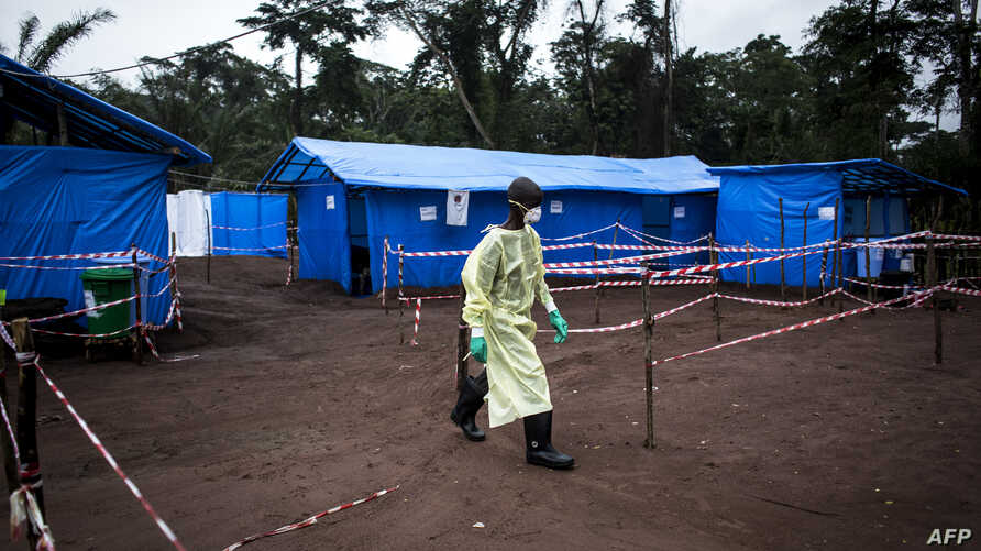 A health worker walks at an Ebola quarantine unit, June 13, 2017 in Muma, DRC, after a case of Ebola was confirmed in the village.