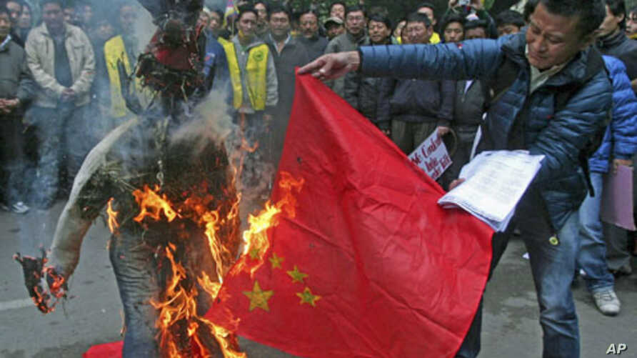 Tibetan exiles burn a Chinese flag and an effigy representing a Chinese official during a protest in New Delhi, January 17, 2012.