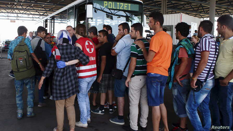Migrants picked up within Austria near the border with Hungary line up at a makeshift camp in Nickelsdorf to be transported to other processing facilities, Aug. 29, 2015.