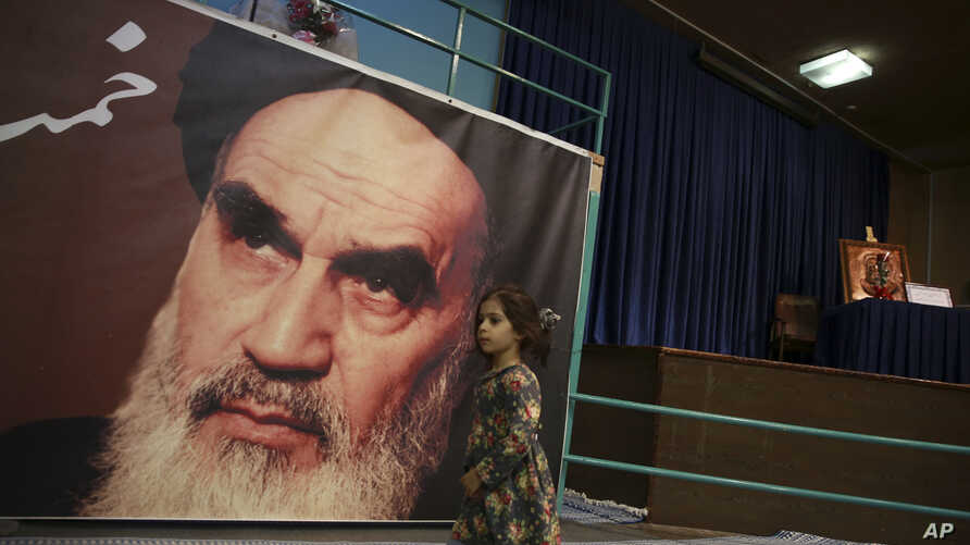 A girl walks past a poster of Ayatollah Ruhollah Khomeini, at a mosque where he made speeches, in northern Tehran, Iran, Jan. 22, 2019.