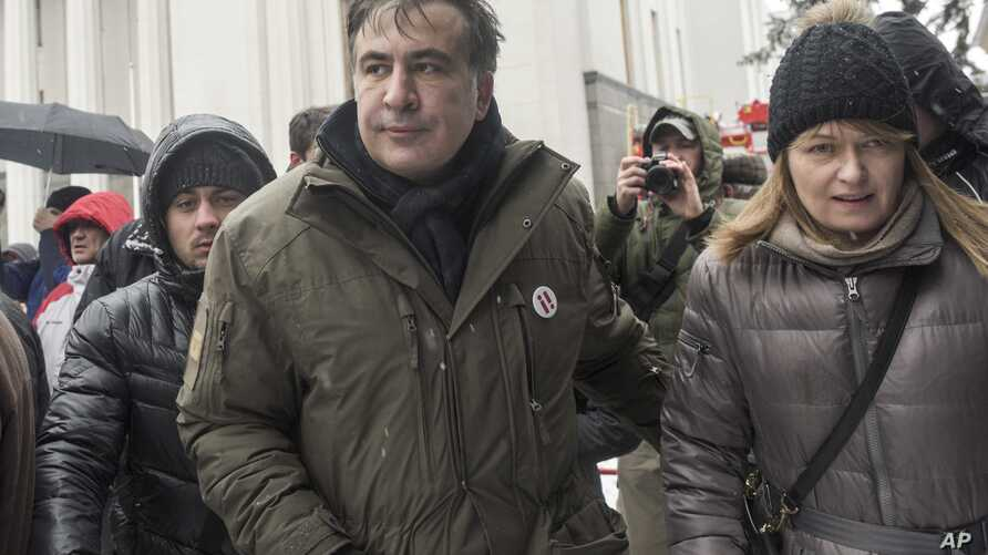 Former Georgian president Mikheil Saakashvili, left, and his wife Sandra Roelofs, right, attend a rally of his supporters as they camp out outside parliament demanding the resignation of the Ukrainian president, in Kiev, Ukraine, Dec. 6, 2017.