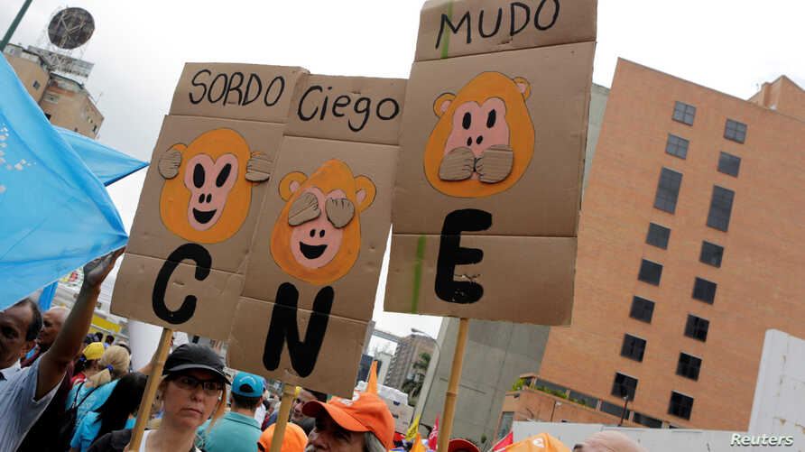 "Opposition supporters hold placards during a rally to demand a referendum to remove President Nicolas Maduro in Caracas, Venezuela, May 14, 2016. From left, the placards read ""Deaf,"" ""Blind"" and ""Dumb."" ""CNE"" on the placards refers to the National El"