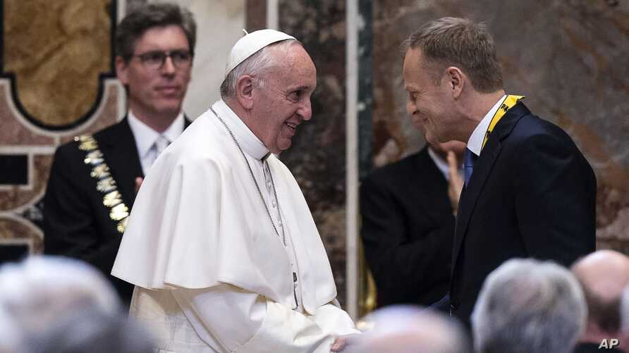 Pope Francis salutes the President of the  European Council Donald Tusk, after receiving the International Charlemagne Prize of Aachen (Karlspreis)  during a ceremony at the Vatican, Friday, May 6, 2016.