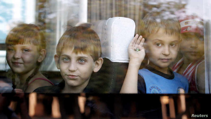 Children who have fled the fighting in eastern regions of Ukraine look out from a mini-bus upon their arrival at a railway station, before leaving for their temporary accommodation, in Stavropol, southern Russia, August 21, 2014.  REUTERS/Eduard Korn