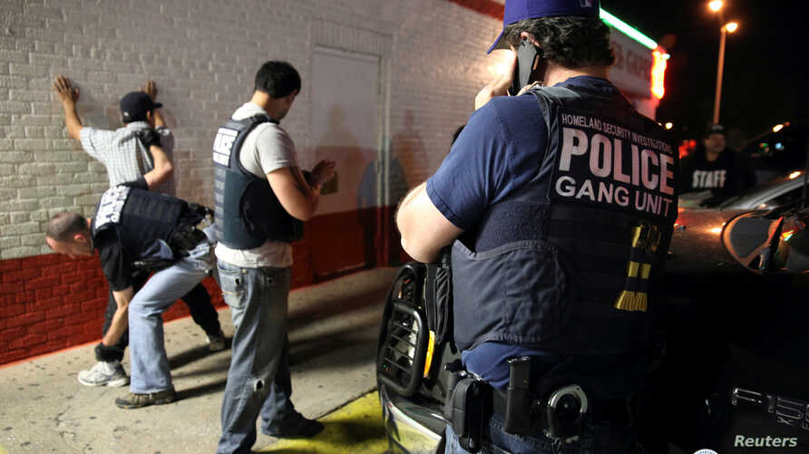 FILE - Federal agents with the U.S. Immigration and Customs Enforcement's (ICE) Homeland Security Investigations (HSI) detain a man in this handout picture taken in Dallas, Texas, March 30, 2014, and released May 1, 2014.