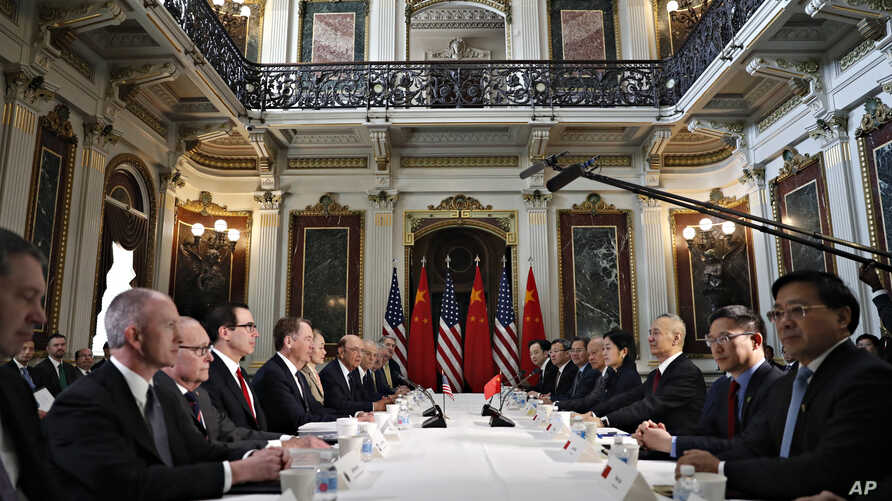 FILE - U.S. and Chinese delegations meet in the Indian Treaty Room in the Eisenhower Executive Office Building on the White House complex, during continuing meetings on the U.S.-China bilateral trade relationship, Feb. 21, 2019, in Washington.