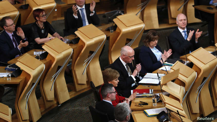 Scottish National Party lawmakers applaud after the vote on a second independence referendum in the Parliament in Holyrood, Edinburgh, March 28, 2017.