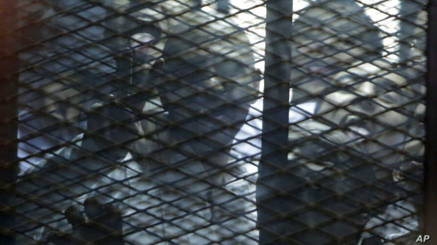 FILE - Egyptian activists are seen through the mesh of a courtroom cage in Cairo, Egypt, Feb. 23, 2015.