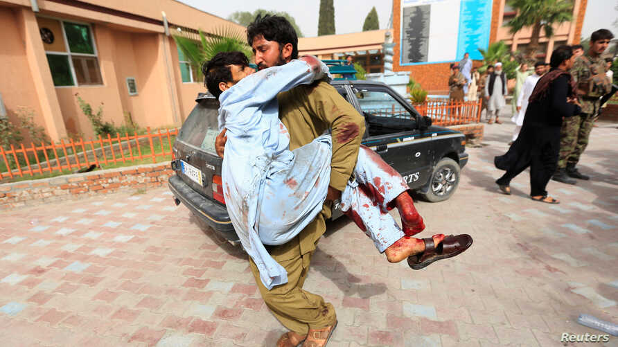 An injured man is carried to a hospital after a car bomb in Jalalabad city, Afghanistan June 17, 2018.