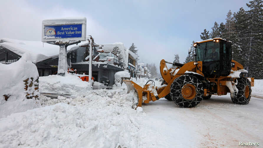 FILE - A plow clears snow after a heavy winter storm in Tahoe City, California, Jan. 11, 2017.