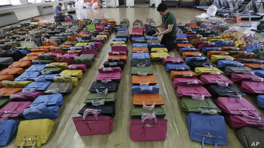 A police official checks some 400 counterfeit bags at the Jungbu police station in Seoul, South Korea, June 1, 2016.