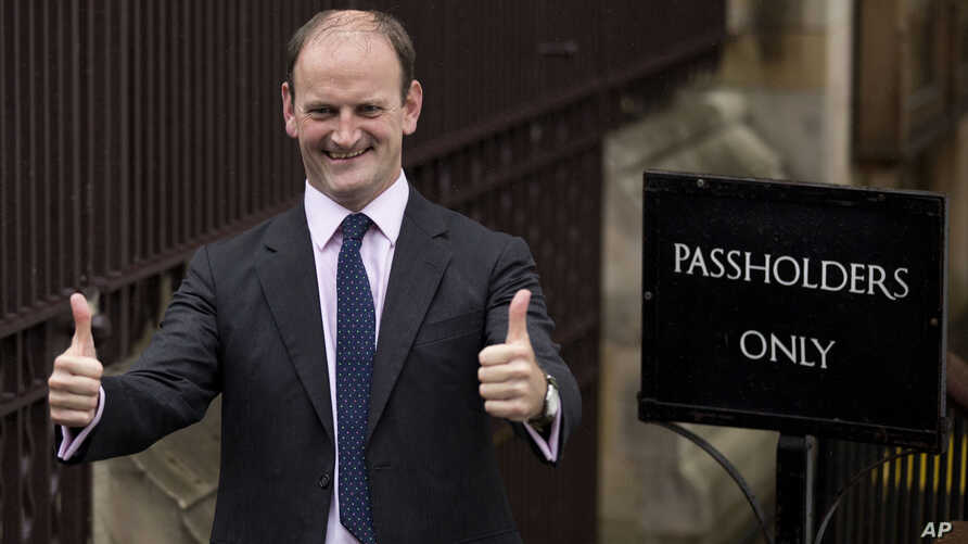 FILE - Douglas Carswell, then newly elected to Parliament as a member of the UK Independence party, gives a double thumbs-up as he arrives to take his seat at the Houses of Parliament in London, Oct. 13, 2014. Carswell said March 25, 2017, that he's