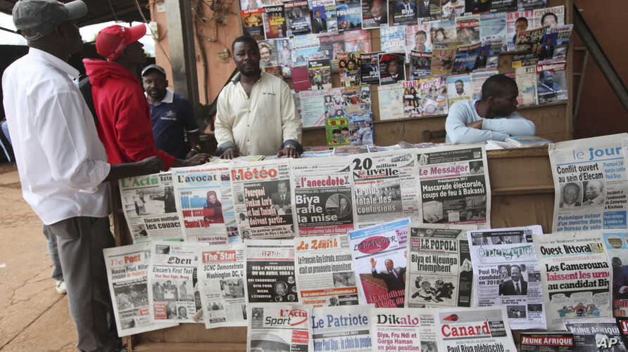 FILE - People read local newspapers with election headlines in Yaounde, Cameroon.