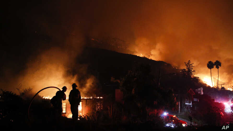 Two firefighters watch as a home burns in a wildfire in La Conchita, Calif., Dec. 7, 2017.