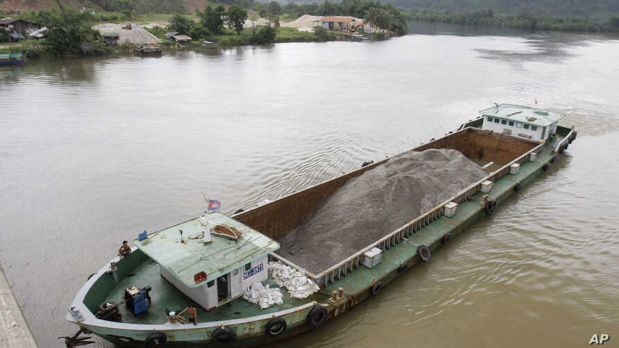 FILE - A Vietnamese vessel hauling sand plies the Tatai River in southwestern Cambodia, Aug. 2, 2011. Cambodia once exported vast amounts of sand for land reclamation and construction projects in Singapore.