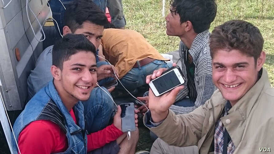 1) Refugees on the Greek island of Chios using information stored on RefuComm's micro SD cards. The cards include video, audio and text information about the interview that those wishing to claim asylum must take.