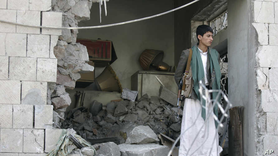 A Yemeni stands guard at the damaged residence of the Iranian ambassador after a car bomb attack in Sanaa, Yemen, Dec. 3, 2014.
