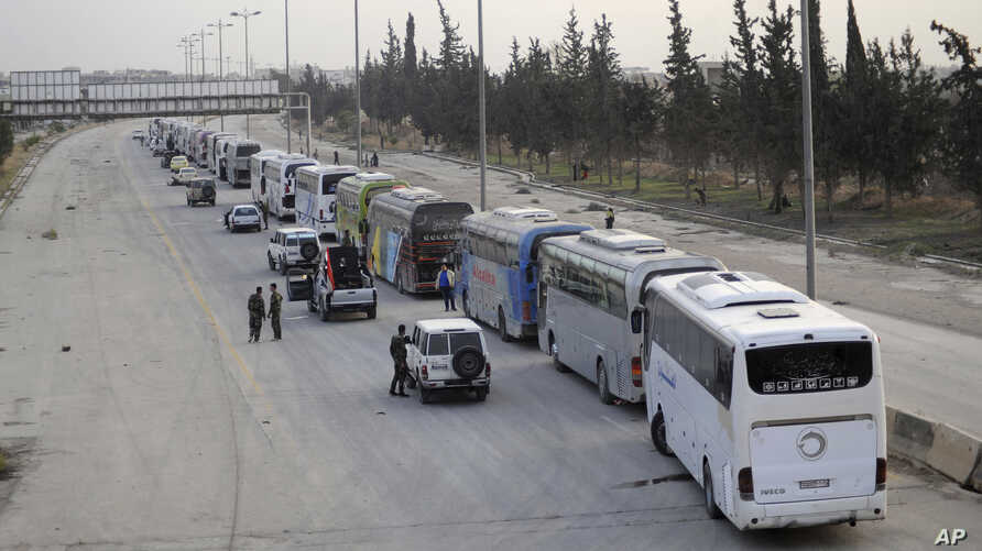 This photo released March, 22, 2108, by the Syrian official news agency SANA, shows Syrian government forces overseeing the evacuation by buses of rebel fighters and their families, at a checkpoint in eastern Ghouta, Syria.